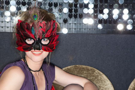 Woman wearing feather mask in bar