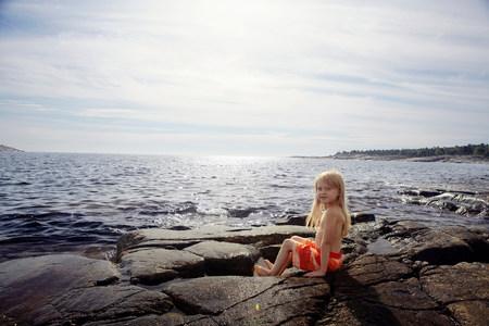 Boy sitting on rocks by lake Standard-Bild