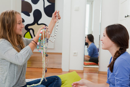 Girls examining jewelry in bedroom