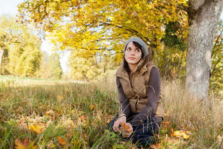 Woman sitting in grass in park Imagens