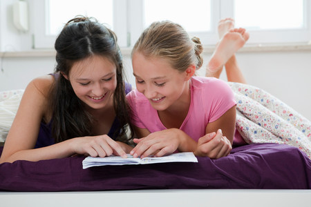 Girls reading together on bed
