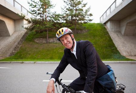 Businessman riding bicycle on street 免版税图像