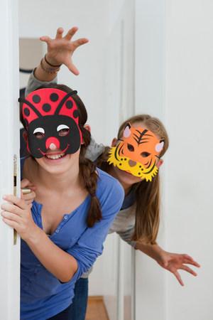 Smiling girls wearing colorful masks Stock Photo