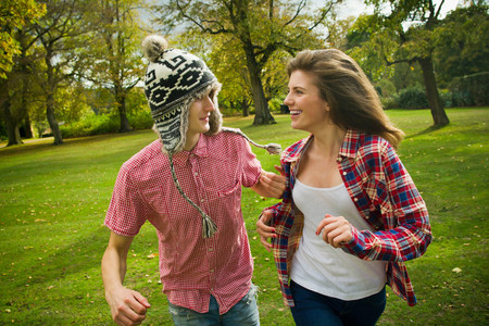 Teenage couple running in park