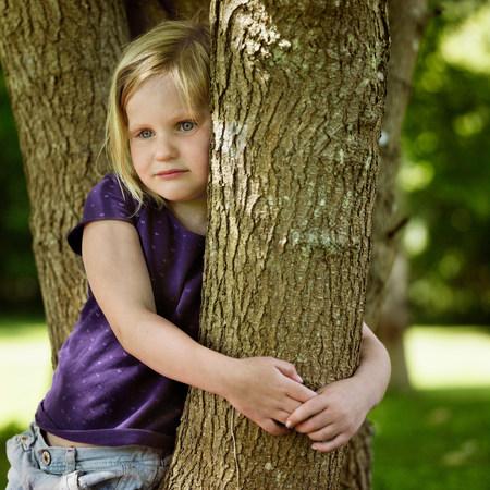 Smiling girl hugging tree