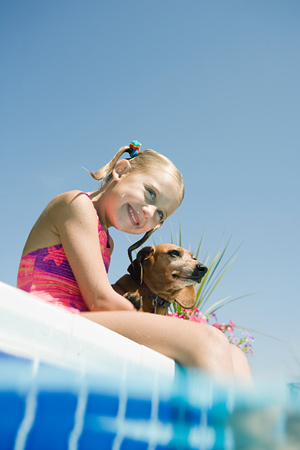 Girl and pet dachshund by pool Stockfoto