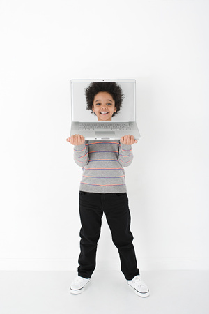 Boy with face on laptop Stock Photo