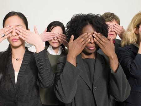 Businesswomen covering eyes