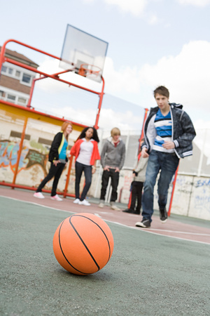 Teenagers in basketball court Stock Photo