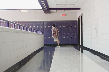 A male high school student running in a corridor Stock fotó