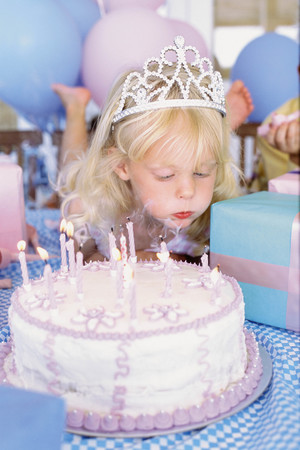 Portrait of a birthday girl blowing the candles