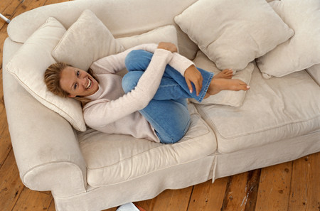 Girl curling up on sofa