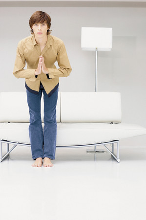 Man bowing in front of modern sofa