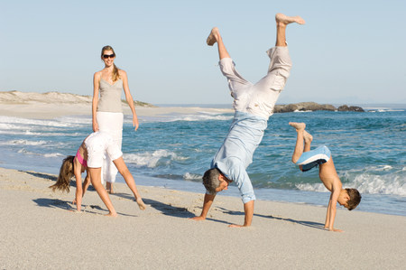 Family doing handstands on the beach