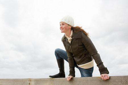 Woman climbing over wall Imagens