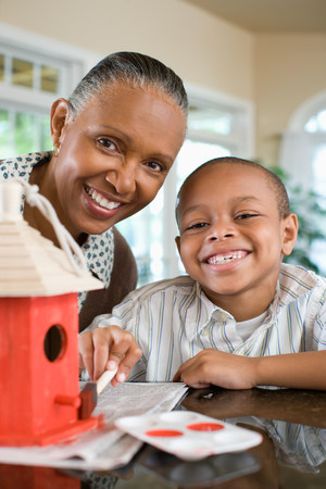 A grandmother and grandson painting a birdhouse