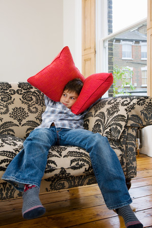 Boy covering his ears with cushions 版權商用圖片