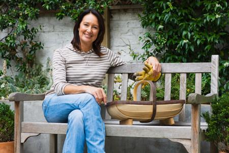 Portrait of a mature woman sat on a bench
