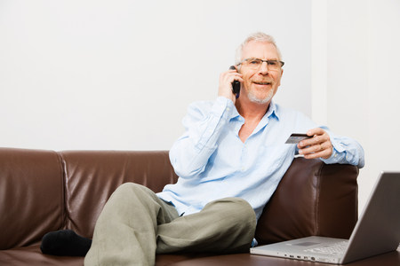Mature man using telephone banking 免版税图像