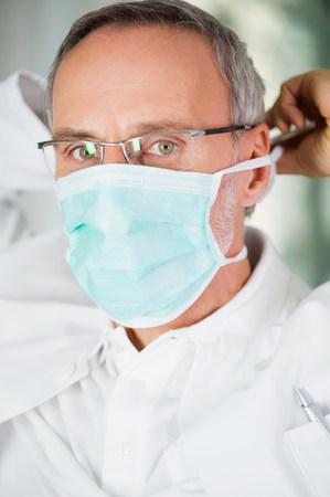Dentist putting on mask