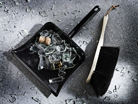 Broken glass and a dustpan and brush