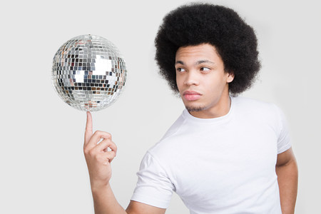 A young man balancing a disco ball