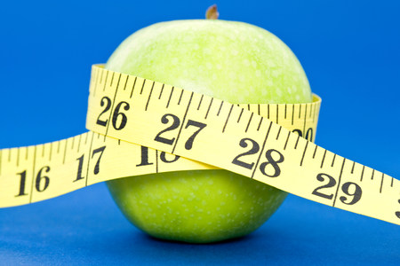 A tape measure wrapped around an apple Stock Photo