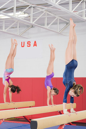 Gymnasts doing handstands on balance beams Stock Photo