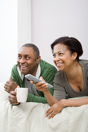 Couple watching television on bed Banque d'images - 117896325