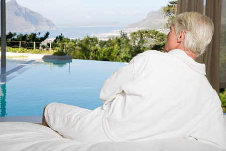 Middle aged man wearing bathrobe lying on bed and looking out at swimming pool Stockfoto
