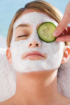 Young woman with facial mask having cucumber slice placed over eye Banco de Imagens - 117896450