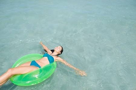 Woman in sea on inflatable ring Imagens