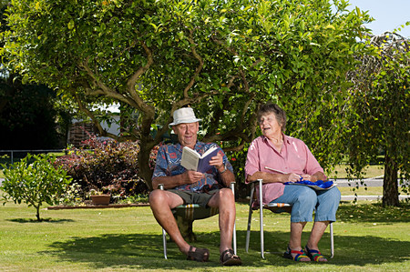 Senior couple relaxing under a tree in the garden
