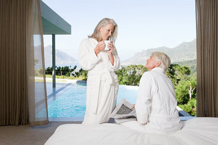Middle aged couple wearing bathrooms in bedroom with view out to swimming pool Stockfoto