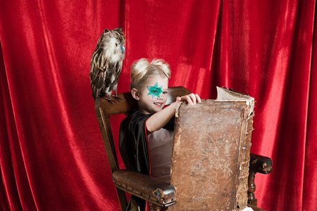 Young girl dressed up as wizard reading spell book