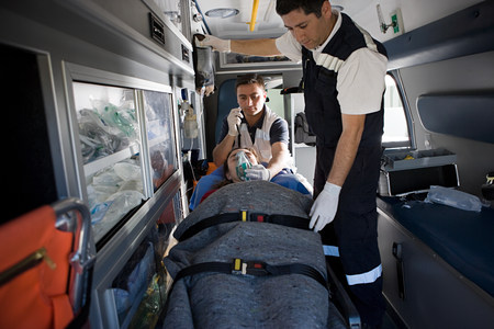 Ambulance staff and patient on stretcher Stock fotó