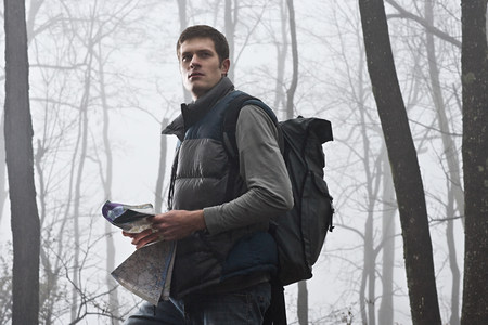 A young male hiker holding a map in a misty forest