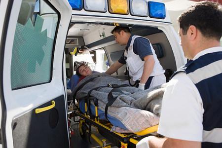 Personel pogotowia i pacjent na noszach