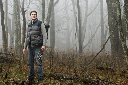 A male hiker standing in a misty forest opening Stockfoto