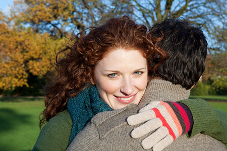 A smiling woman looking over the shoulder of her partner Stock Photo