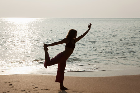 Woman practicing yoga by sea ay sunset Stock Photo