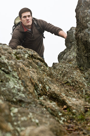 A male hiker emerges from climbing a forest cliff edge