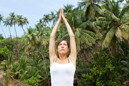 Woman practicing yoga by palm trees Imagens