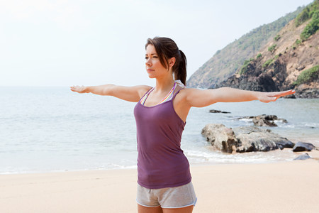 Woman practicing yoga by sea Imagens
