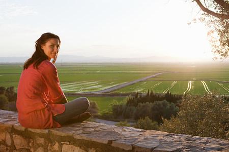 Young woman sitting on stone wall 版權商用圖片