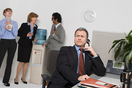 Businessman on telephone with people gossiping by water cooler Reklamní fotografie