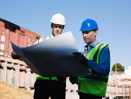 Mature men inspecting blueprints on construction site