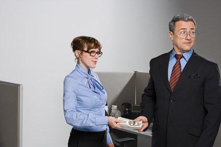 Businessman handing over money to businesswoman