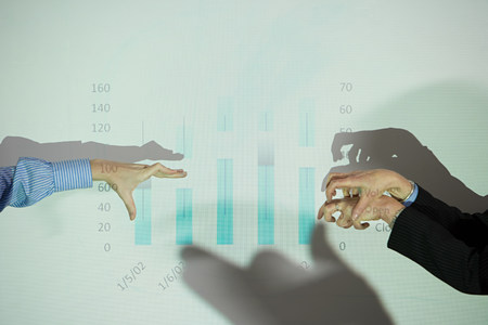 Businessmen doing shadow puppets in front of whiteboard Stock Photo