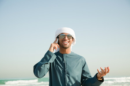 Middle Eastern man using mobile phone on the beach Imagens